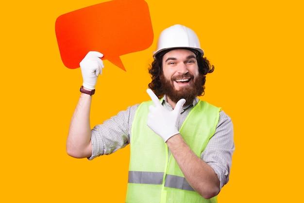 Улыбающийся молодой архитектор держит пузырек с речью и смотрит в камеру, указывая на него возле желтой стены
