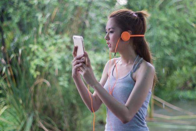 Улыбающаяся молодая азиатская женщина слушает музыку на своем мобильном телефоне в головном телефоне.