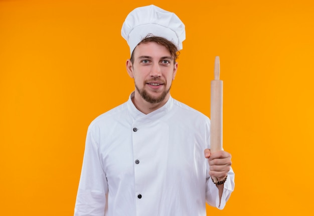 オレンジ色の壁を見ながら麺棒を保持している白い制服を着た笑顔の若いひげを生やしたシェフの男