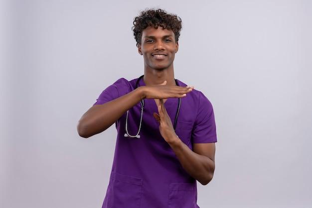 Улыбающийся молодой красивый темнокожий доктор с вьющимися волосами в фиолетовой форме со стетоскопом показывает символ, выражающий просьбу о времени