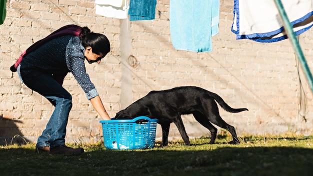 庭で黒い犬と遊んでいる間、乾くために服をぶら下げている笑顔の若い男