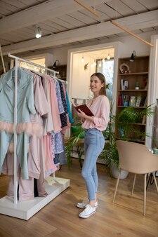 Улыбающийся молодой стилист выбирает одежду для идеального сочетания
