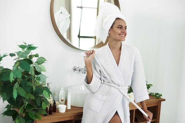 Улыбающаяся молодая женщина только что вышла из душа и стоит в ванной. уход за кожей, утренний распорядок.