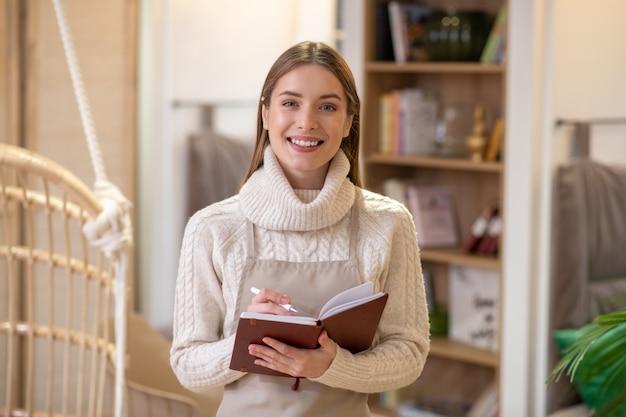 彼女の計画とノートを保持している笑顔の若い女性