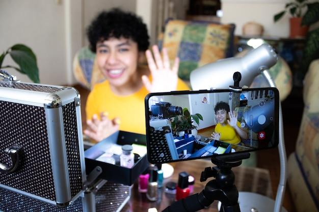 Улыбающаяся молодая женщина, показывающая накрашенные ногти перед камерой мобильного телефона, с посудой для ухода за ногтями, сидит в гостиной