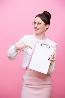 眼鏡をかけた笑顔の若い女性は彼女の手でクリップボードフォルダーを保持
