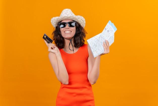 地図とクレジットカードを保持している太陽の帽子とサングラスを身に着けているオレンジ色のシャツの短い髪の笑顔の若い女性