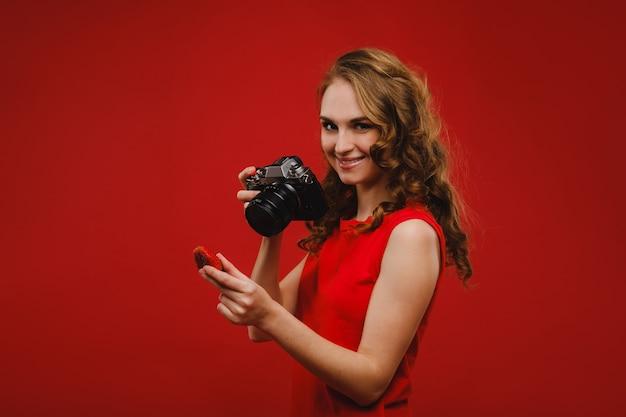 물결 모양의 머리를 가진 웃는 젊은 여자가 딸기를 보유하고 밝은 빨간색 배경에 맛있는 신선한 딸기를 들고 사진을 찍습니다.