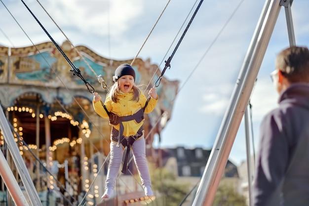 Улыбающаяся девочка прыгает на батуте со страховкой.