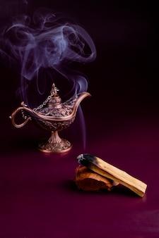 어두운 배경에 동양 아로마 램프가 있는 팔로 산토 나무의 흡연 막대기