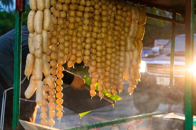 Продавец закусок на велосипеде продает еду под дождем.