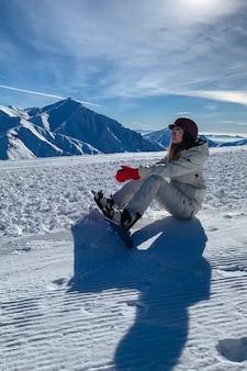 Девушка-сноубордист сидит на склоне горы, расслабляясь и отдыхая на красивом снежном склоне горы.