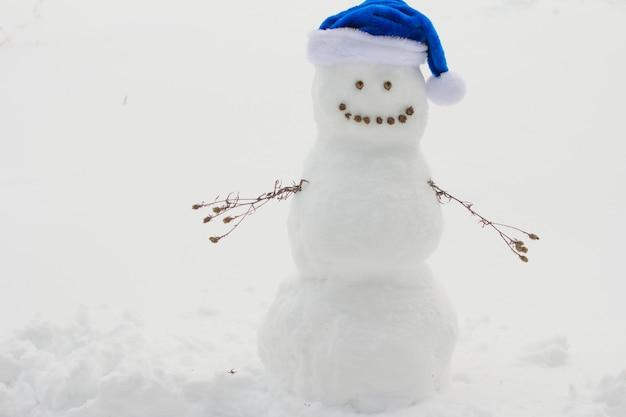 산타클로스 모자를 쓴 눈사람. 하얀 눈에 새해 크리스마스