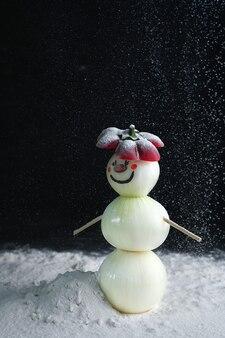 真珠玉ねぎで作った雪だるまが雪の上に立っています。
