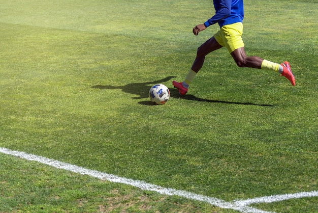 サッカー選手がクローズアップの自然の芝生のフィールドでボールを蹴る準備をします