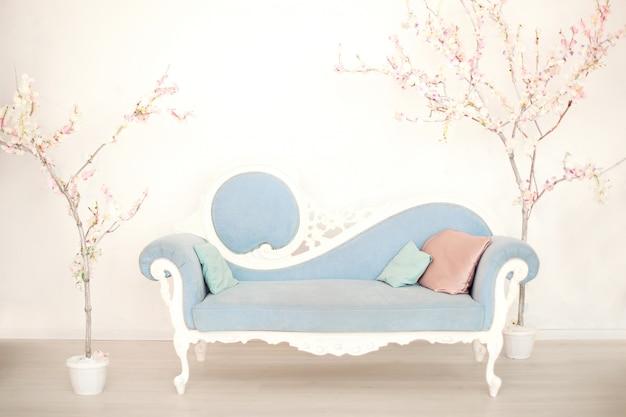 白いリビングルームの人工花木が付いている柔らかい青いソファー。家の中で古典的なスタイルのソファ。ビンテージルームのアンティーク木製ソファアームチェア。春の時間!パステルルーム。リビングルームのインテリア