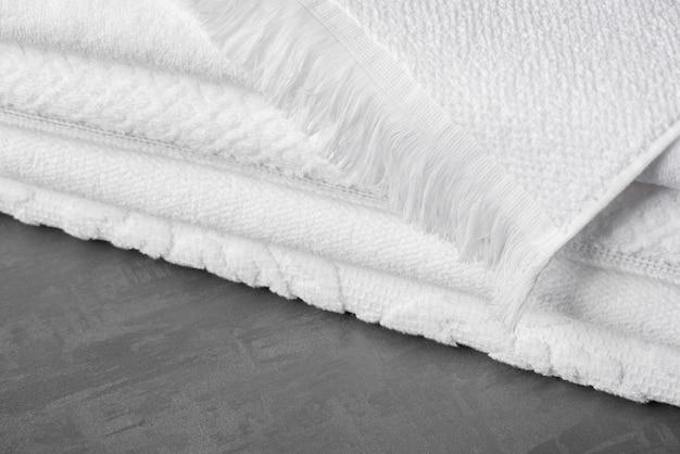 회색 표면에 부드러운 접힌 목욕 수건, 클로즈업
