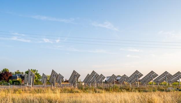Солнечная электростанция с панелями устанавливается перед сельским домом, чтобы обеспечить его всем необходимым электричеством.