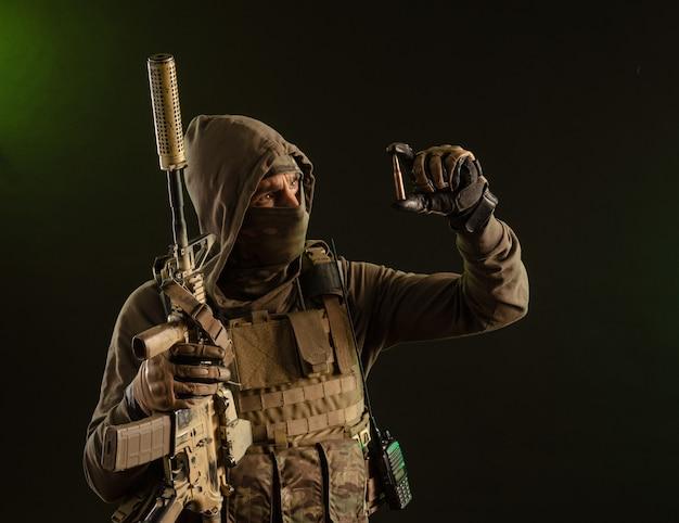 어두운 배경에 무기를 든 군복을 입은 군인 파괴자는 총알을 보여줍니다