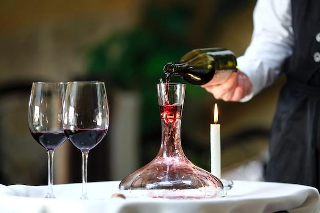 Сомелье наливает красное вино в графин