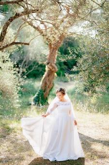 세련된 신부가 빛이 넘치는 숲 사이의 올리브 숲에 서서 드레스 가장자리를 잡고 있습니다.