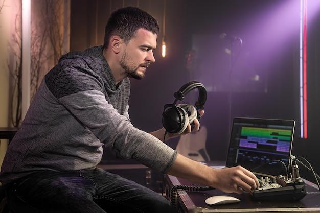 Звукорежиссер со студийными наушниками в руке настраивает звуковой микшер. концепция профессиональной записи.