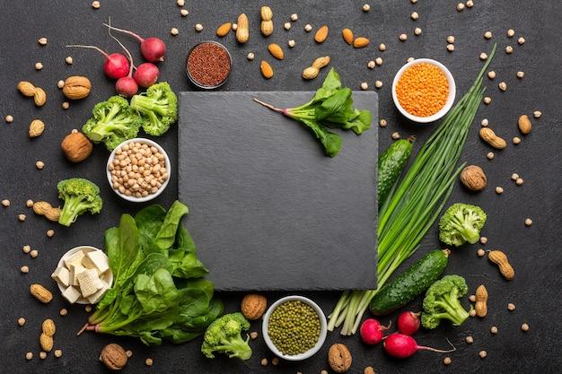 Источник белка для вегетарианцев. здоровая чистая пища: вид сверху зелени, овощей, орехов и бобовых на черном фоне с черным режущим камнем в центре.