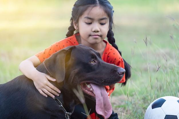 저녁에 뒷마당 잔디밭 밖에 있는 커다란 검은 개와 축구를 하는 동남아 소녀. 애완 동물 애호가 개념