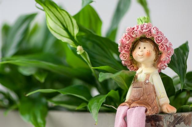 Сувенирная статуэтка девушки, сидящей на фоне листвы