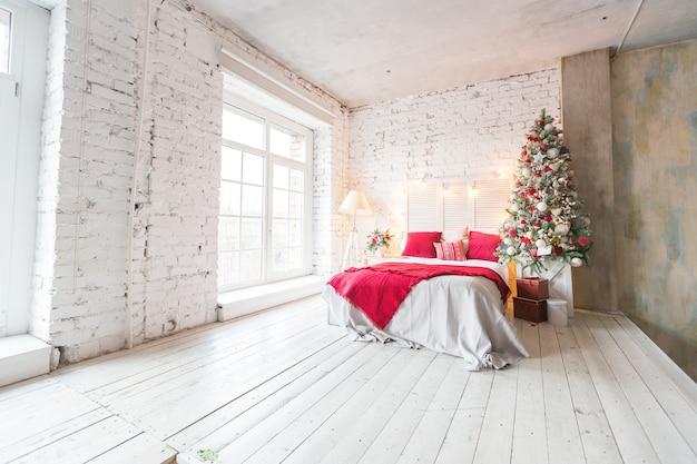장식 된 크리스마스 트리와 화환이있는 로프트 스타일의 넓은 흰색 조명 침실입니다.