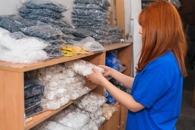 倉庫で商品を積み重ねる青いシャツを着ているスペインの若い女性