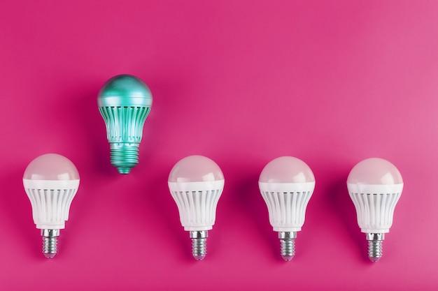 특수 전구는 분홍색 벽에 일반 흰색 전구 그룹에서 두드러집니다.
