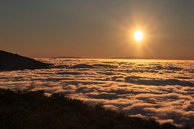 Эффектный закат над облаками в национальном парке вулкана тейде на тенерифе. прекрасный закат на канарских островах.