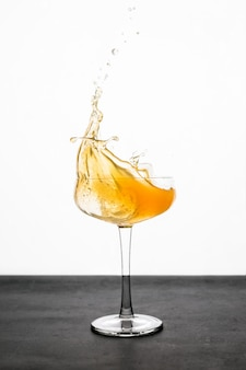 Всплеск апельсинового коктейля в бокале купе