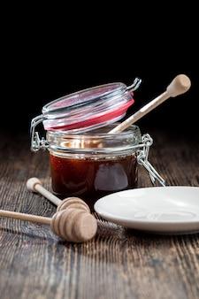 고품질의 벌꿀과 함께 꿀을 담을 수 있는 숟가락, 건강하고 달콤한 벌꿀이 놓여 있는 오래된 탁자, 꿀을 옮기고 부을 수 있는 수제 나무주걱