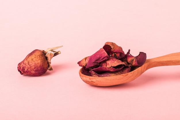 ピンクの表面に乾燥した花びらとしおれたバラのつぼみが付いたスプーン