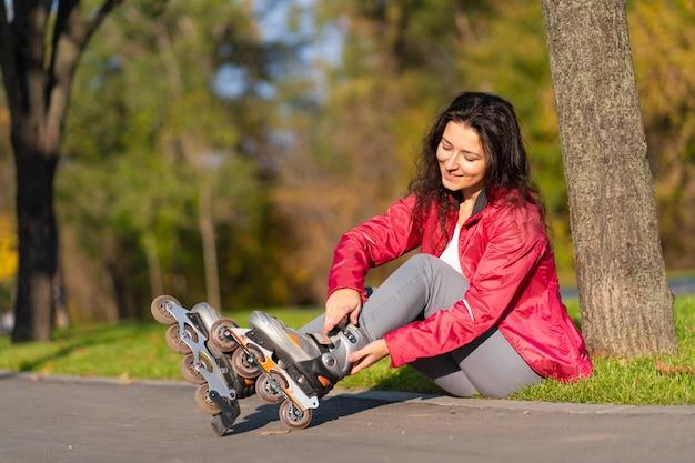 陽気な女の子が秋の公園でローラーブレードをしている