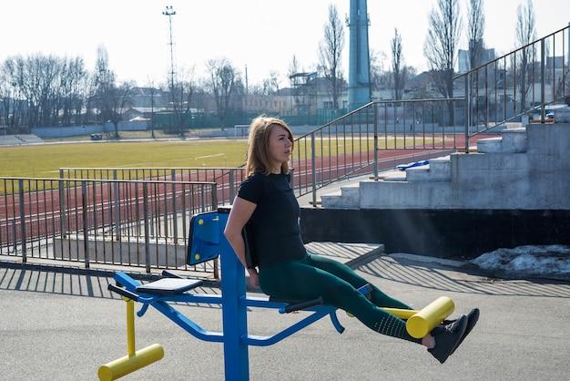 スポーツの女の子は、新鮮な空気の中でシミュレーターやダンベルを使って足を鍛えます。スポーツ、フィットネス、健康的なライフスタイルのコンセプト。