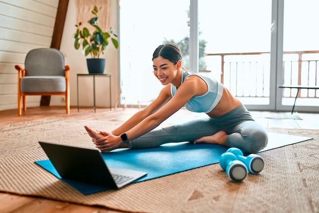 운동복을 입은 낚시를 좋아하는 여성이 운동을하고 근처에 덤벨을 눕히고 거실에서 집에서 노트북을 사용합니다. 스포츠 및 레크리에이션 개념.