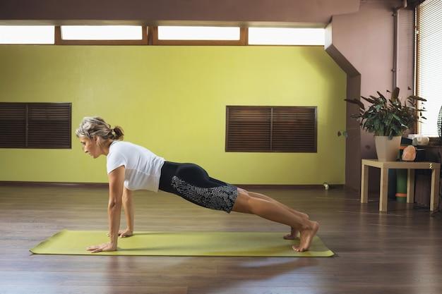 ヨガを練習しているスポーティーな女性は、スタジオで板のポーズであるファラカサナエクササイズを行います