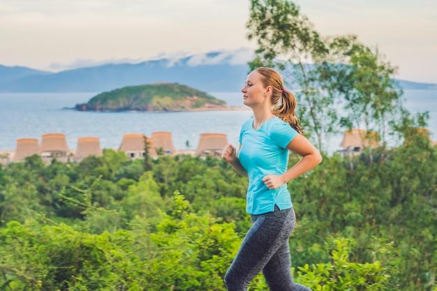 陽気な若い女性が海に向かって走っています。