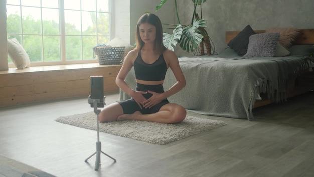 スポーツガールのブロガーが、電話でオンラインで正しく呼吸する方法を教えています。