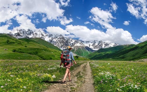 Спортивная девушка в шляпе с рюкзаком идет по красивой горной дороге с видом на ледник грузия сванетия.