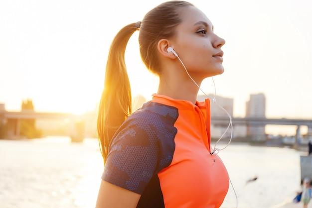 スポーツの女の子が川岸の街を走りながらヘッドフォンで音楽を聴く