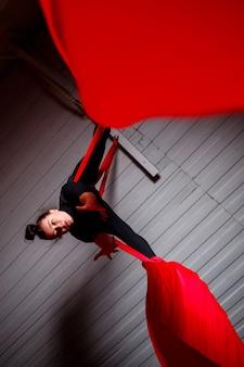 スポーツガールは赤い絹で体操とサーカスの練習をします。暗い背景でのスタジオ撮影。キャンバス上の空中体操