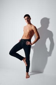 Спортивный парень в брюках стоит на одной ноге против света в полный рост.