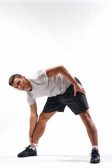 ショートパンツとフルレングスのtシャツを着たスポーツマンがライトでエクササイズをします。
