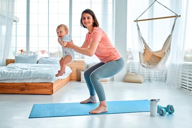 Спортивная мама занимается с ребенком фитнесом и йогой дома. понятие о спорте, материнстве и активном образе жизни. молодая женщина в спортивной тренировке с ребенком.