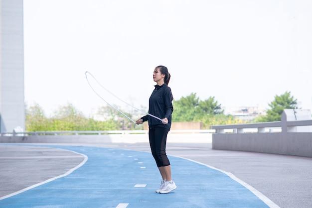 Спортсменка упражнения с прыжками через скакалку на беговой дорожке.