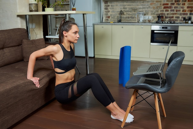 Спортивная девушка в черном обтягивающем костюме тренирует трицепсы и грудь и смотрит онлайн-тренировочное видео на ноутбуке. тренер-женщина проводит удаленное домашнее занятие по фитнесу.